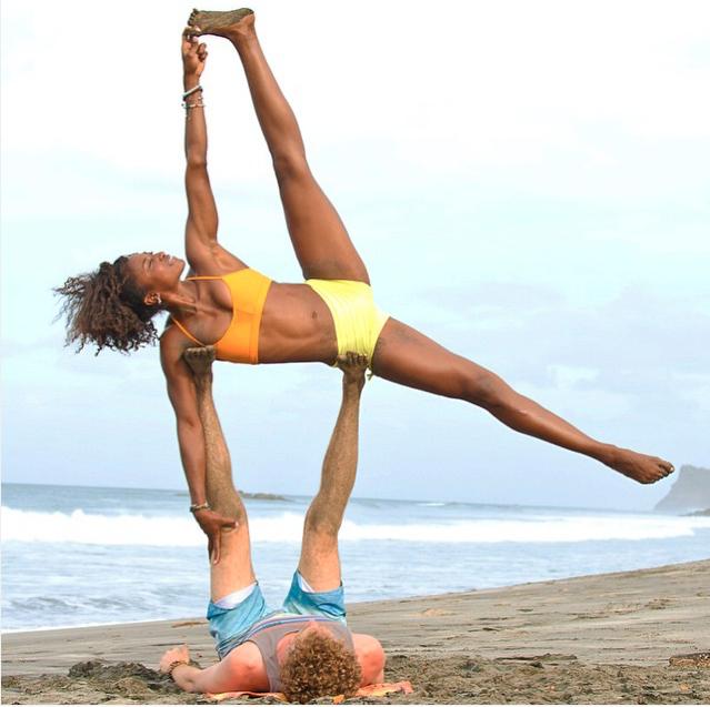 Koya and her partner practice a tricky acroyoga move on the beach.