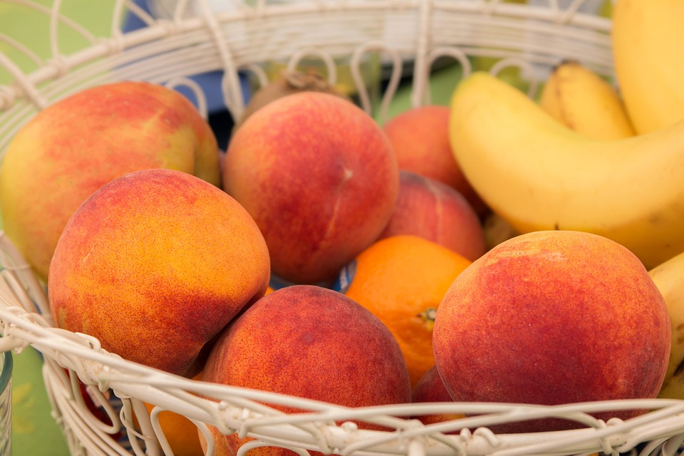 a basket full of fresh peaches, oranges and bananas